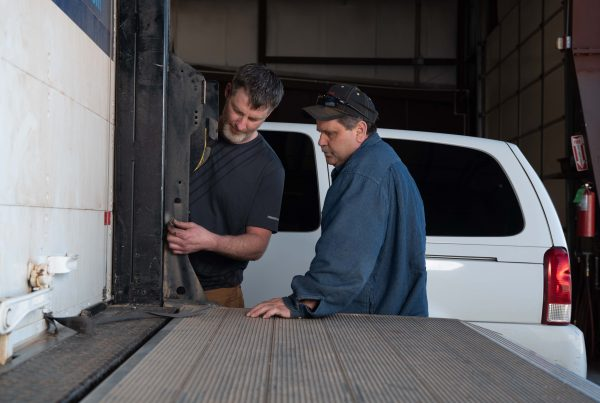 two men evaluate truck door and lift gate