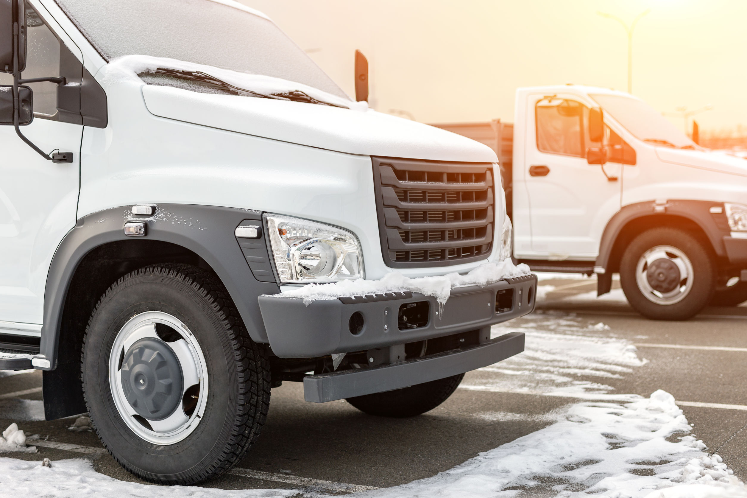 New middle size trucks at dealership parking outdoors at winter. Truck service and maintenance. Delivering and warehouse service.